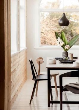 Soggiorno in stile Japandi con accostamento legni chiari e scuri e sedie diverse