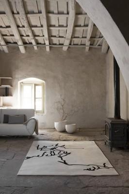 Zona giorno instile wabi-sabi: travi irregolari sul soffitto, pavimento in pietra