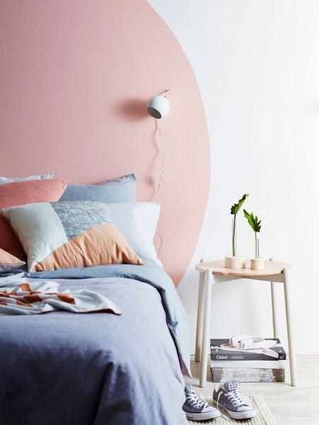 Una testiera dipinta facendo un enorme cerchio rosa sul muro
