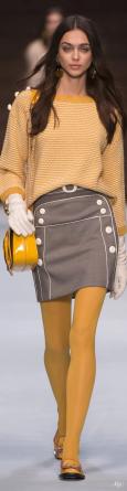 Modella con calze, pull e borsa giallo saturo della collezione autunno inverno 2018/19 di Elisabetta Franchi