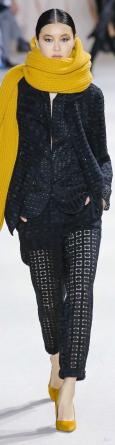 Modella vestita in nero con sciarpa e décolleté giallo zafferano di Akris RTW