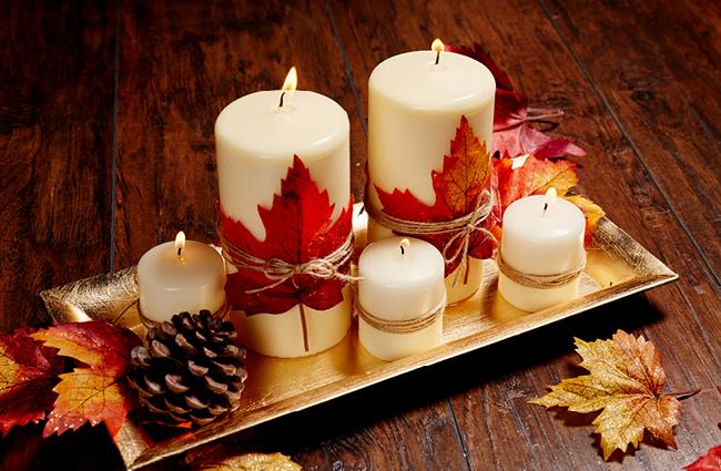 Centrotavola con candele bianche, foglie e pigne