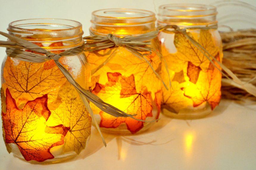 Lanterne con vasetti di vetro e foglie autunnali