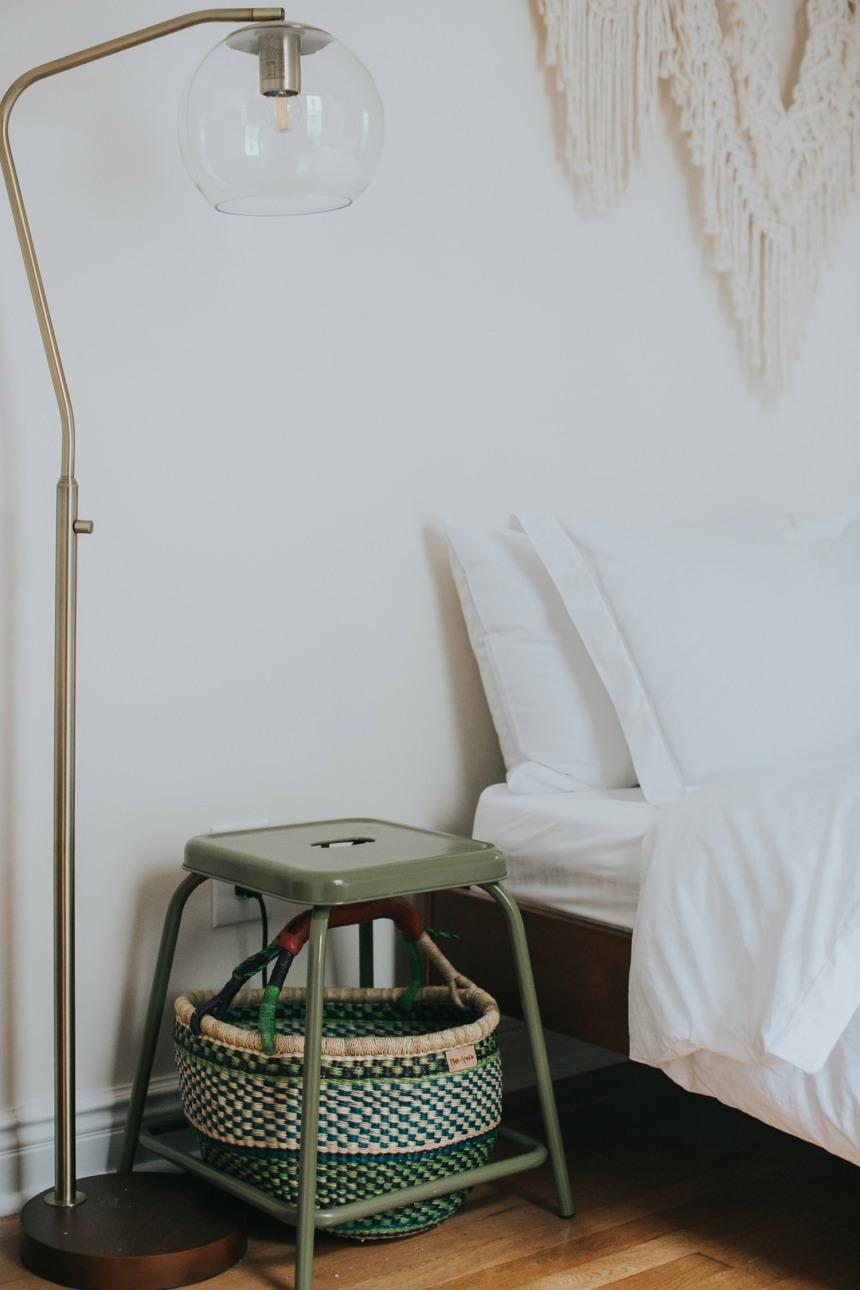 Particolare della camera da letto: comodino fatto con sgabello e cesto più piantana