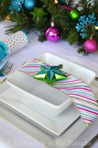 Dettaglio tavola colorata con piatti in ceramica bianca, nastro multicolore e stella verde e blu