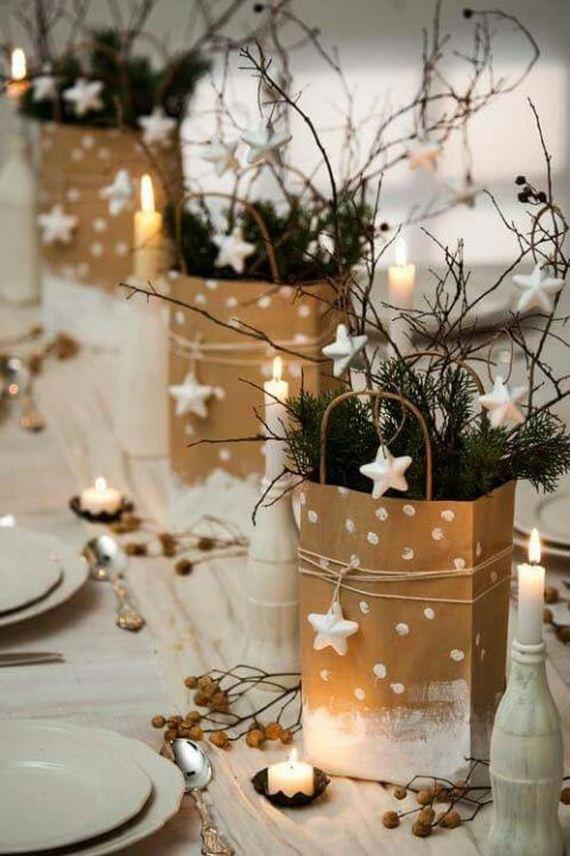 Tavola apparecchiata con piatti bianchi e con sacchetti in carta craft come centro tavola con rametti e stelline