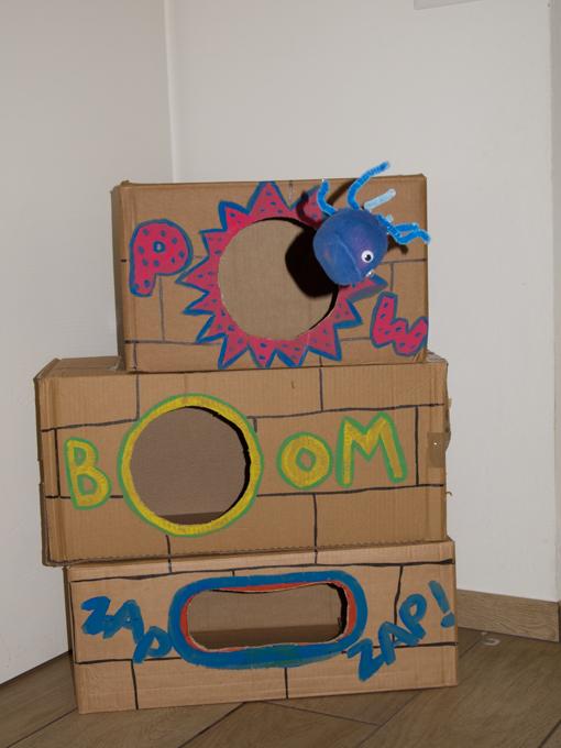 Been bag rivisitato: muro di scatoloni con ragnetti con cui fare centro nei fori