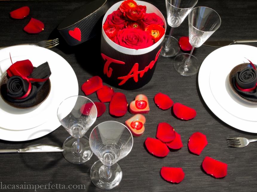 Tavola apparecchiata con runner nero, petali di rosa rossi e una Flower Box con Rose e Ranuncoli rossi