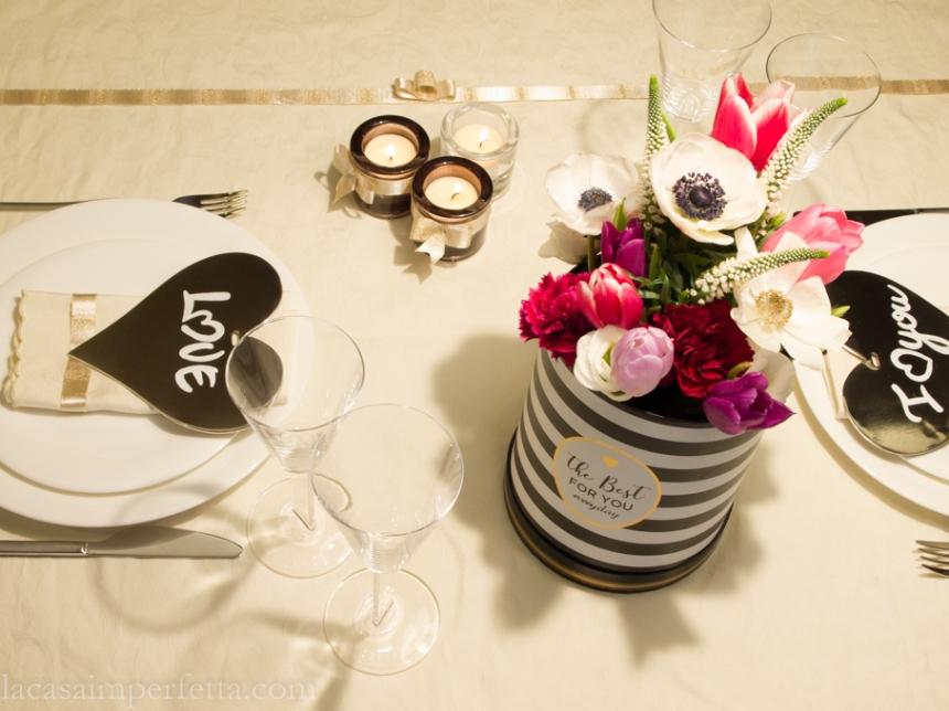 Tavola apparecchiata in bianco e oro con fiori sui toni del rosa e del bianco