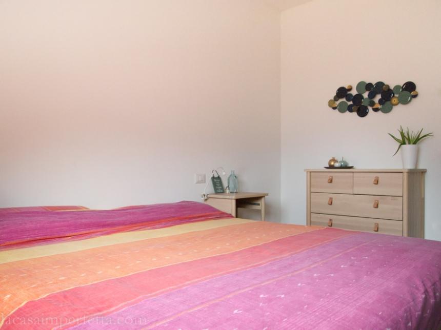 Una camera matrimoniale con letto senza testiera e qualche complemento d'arredo sparso