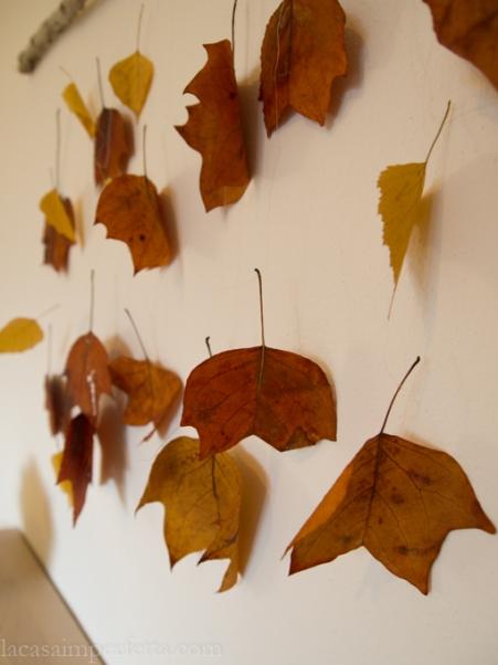 Decorazione da parete con foglie autunnali e ramo caduto