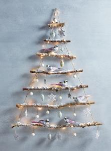 Albero a parete costruito con una corda, dei rami raccolti, addobbi e neve artificiale