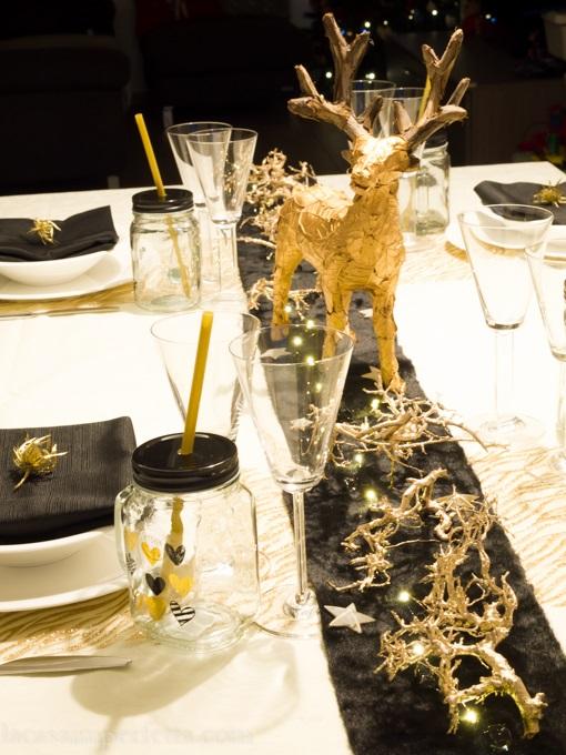 Dettaglio della tavola nera e oro con focus su renna con foglie dorate