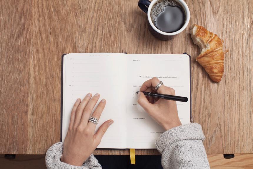 Mani di donna che scrivono su un'agenda per pianificare la settimana
