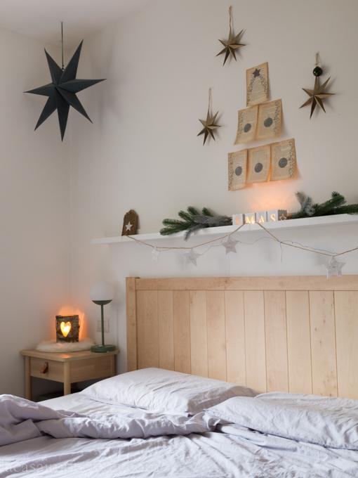 Camera da letto con ghirlanda, candele, stelle ed albero di Natale creato con pagine di vecchio libro