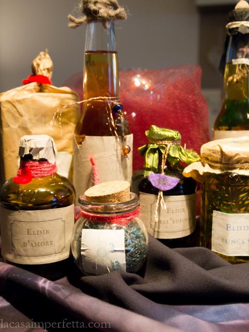 Primo piano di vasetti e bottiglie di vetro con pozioni varie, sullo sfondo la sfera di cristallo