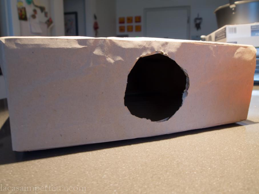 Fase di creazione della mistery box a forma di libro. Scatola chiusa con fori laterali e rivestita da carta da pacco marroncina