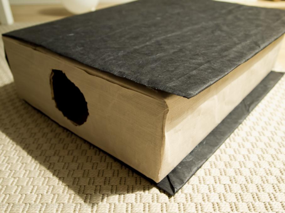 Fase di creazione della mistery box a forma di libro. Scatola chiusa con fori laterali, rivestita da carta da pacco marroncina e foderata con carta di riso nera