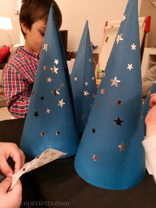 I bambini decorano ognuno il proprio cappello con delle stelline adesive