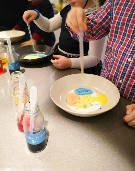 Bambini che giocano con le boccette di vetro con colore alimentare e aceto; piatto con bicarbonato e pipette di plastica