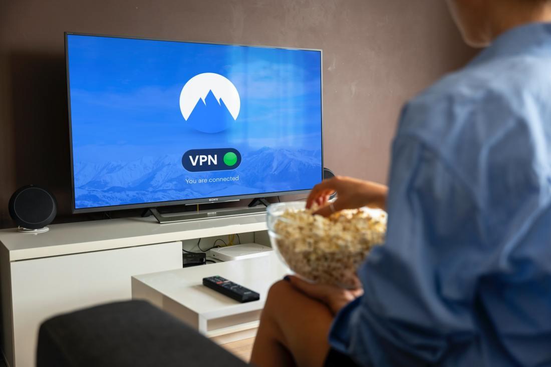 Immagine di una persona seduta sul divano con dei pop corn, davanti a una smart TV che avvisa l'avvenuta connessione tramite VPN